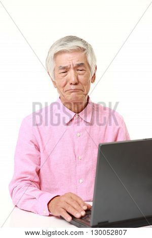 portrait of senior Japanese man using computer looking confused on white background