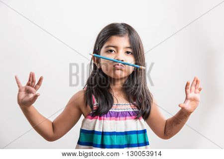 Naughty little indian girl holding a pencil like a mustache. Concept of education. asian girl holding pencil like mustache, isolated over white background