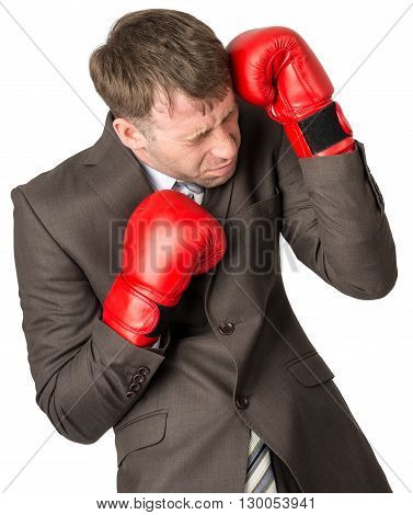 Businessman with boxing gloves defending against white background, close up view