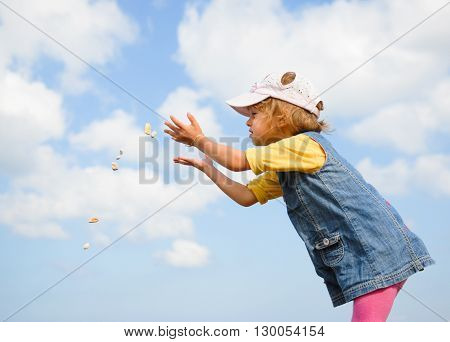 little girl throws stones standing against the sky