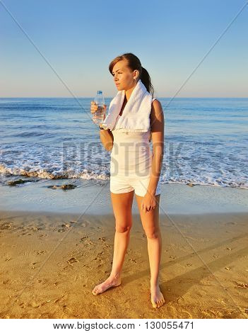 Beautiful Girl Drinking Water After Exercise On Beach