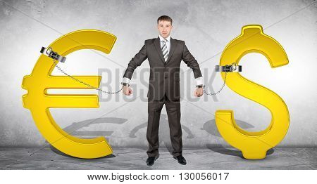 Man chained with golden dollar and euro signs on grey bckground