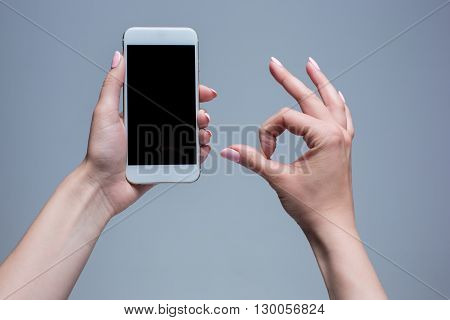 Closeup shot of a woman typing on mobile phone on gray background. Female hands holding a modern smartphone and pointing with figer. Blank screen to put it on your own webpage or message.