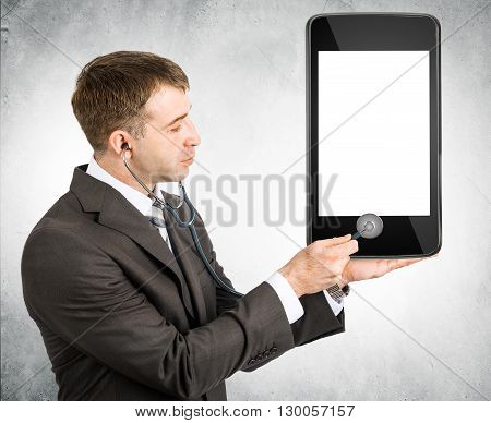 Businessman listening to smartphone within stethoscope, cure concept