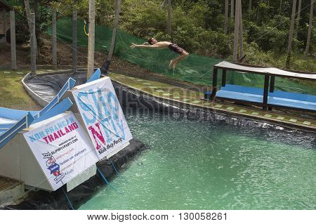 KOH PHANGANTHAILAND - NOVEMBER 25 2014 : Unidentified man jump in the pool in the attraction Slip N Fly on island Koh Phangan