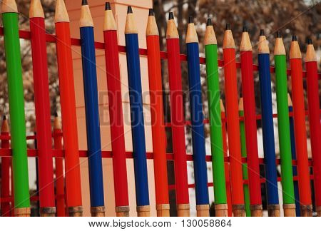 Line up colorful pencils at the balcony's barrier
