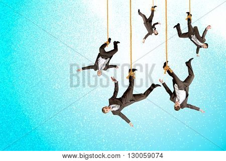 Businessmen hanging on ropes, place image of your product underneath them