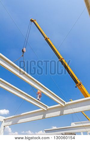 Height worker is high up on concrete frame without proper safety equipment.