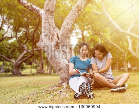 Two women reading a book together with happiness and relax feeling at the garden under sunlight with warm / soft color tone