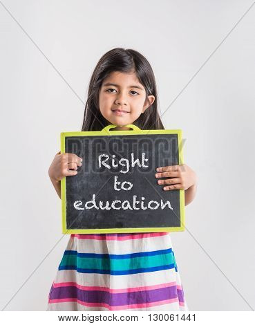 small indian girl holding school slate board, right to education concept, girl education in india concept, asian girl and school slate board