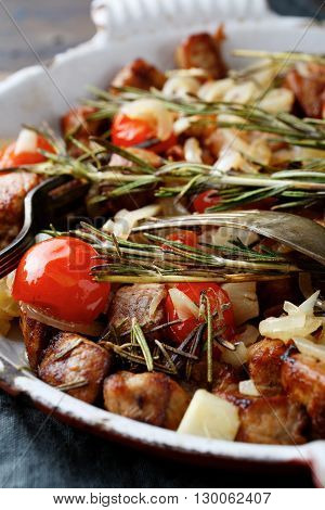 Closeup Of Roasted Pork Meat With Tomatoes And Spices On Pan
