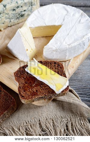 Camembert, Roquefort, Rye Bread Slices And Honey On A Board