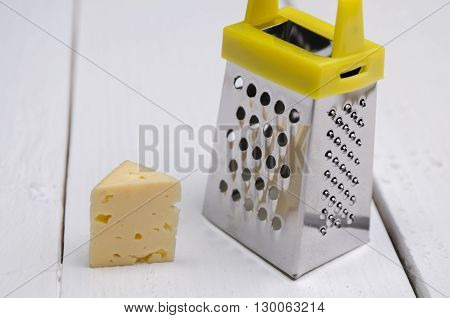 cheese with a grater on a wooden table