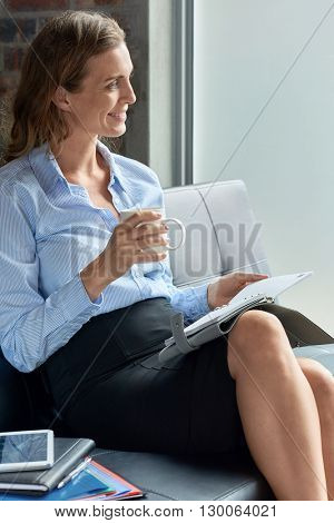 Candid moment of smiling middle age business woman having coffee
