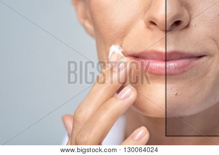 anonymous woman applying face cream, studio beauty skin care concept