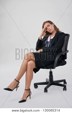 Stressful businesswoman sitting in office chair, having a bad headache migraine