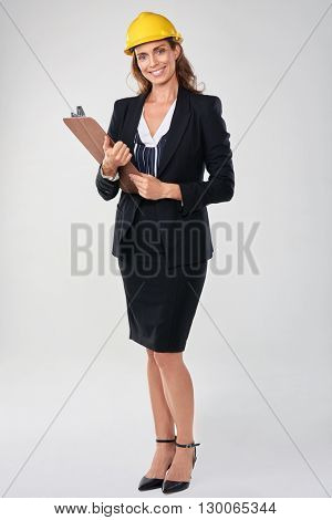 Woman wearing hardhat safety helmet holding clipboard, architect surveyor engineer professional