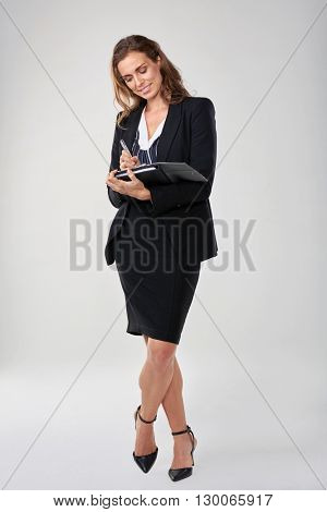 Full length portrait of executive secretary taking notes in an organiser dairy