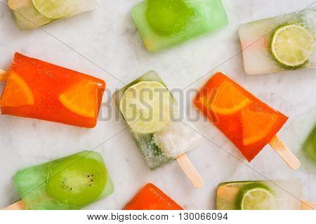 Some fresh fruit popsicles on white marble