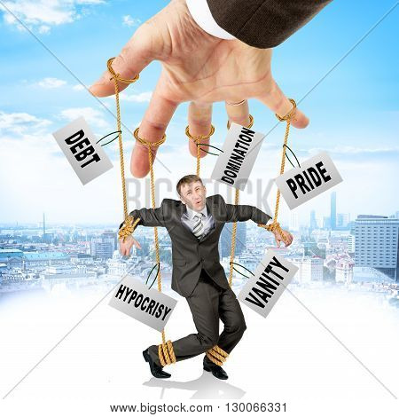 Image of businessman hanging on strings like marionette with words among clouds