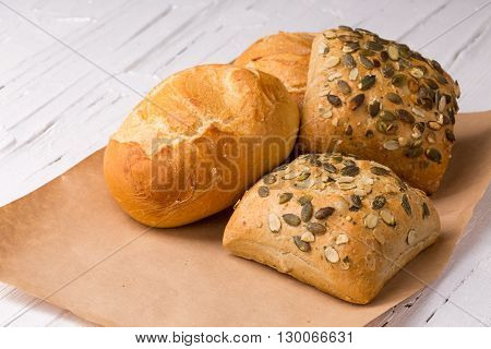 Small group of buns wrapped brown paper on white wooden background.