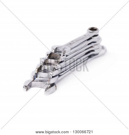 Stack of wrenchs chrome metal spanner instruments isolated over white background