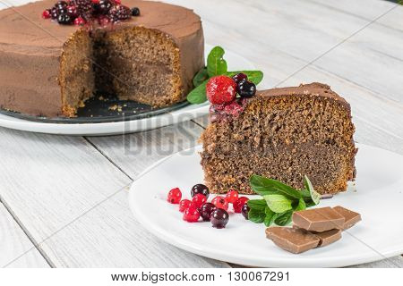 Piece of Chocolate cake with Ganache and berries (strawberries blueberries blackberries and rapsberry) fruit