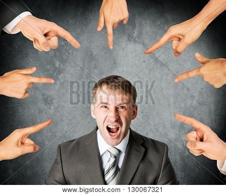Many fingers pointing at screaming stressed businessman on grey background