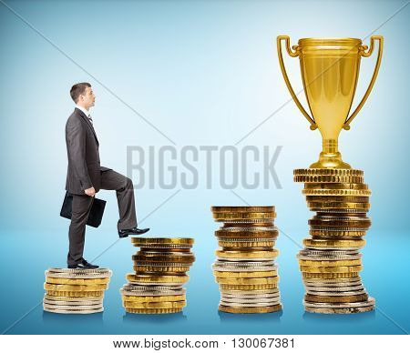 Businessman going up on coin stairs to gold cup