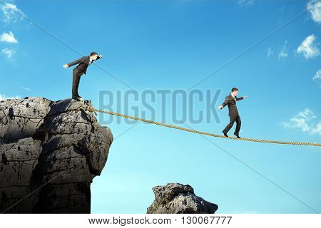 Conceptual image of businessman walking on rope above gap in sky