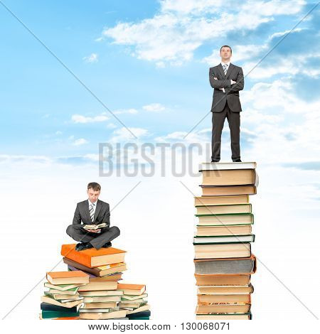Businessman sitting on stack of books and reading opened book, another man standing on books