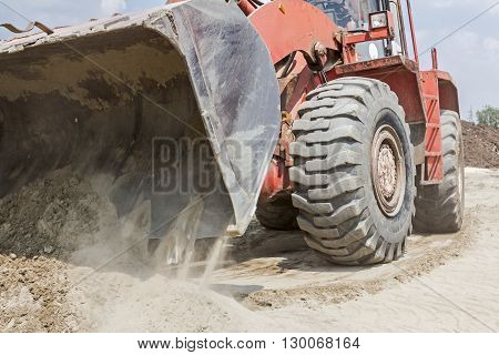 Red loader with wheels at earthmoving works. Bulldozer is pushing sand on huge pile.