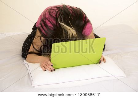 A woman sitting in her bed with a laptop she has had enough she puts her head down on the laptop.