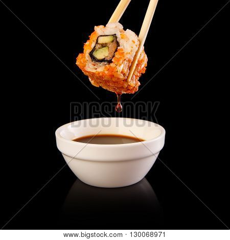 A delicious sushi roll dipped in sauce on a black background.