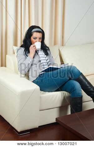 Woman On Sofa Drinking Coffee And Reading