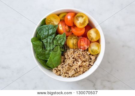 Quinoa salad with vegetables on marble table