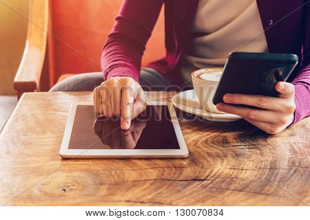 Woman Hands Using Computer Tablet And Holding  Smartphone In Coffee Shop With Vintage Toned.