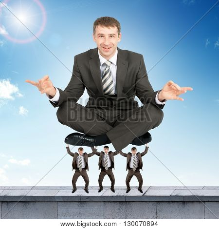 Young businessman sitting in lotus posture on little men