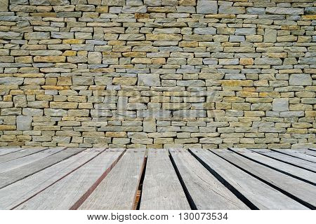 Stone wall background or texture with wooden walkway.
