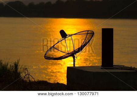 Satellite dish on the reflection on the river in sunset background.