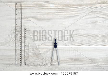 Flat lay of riangle centimeter ruler, simple centimeter ruler and engineering divider on wooden surface. Top view composition. Working stuff. Work place of draftsman, architect, constructor. Engineering work. Construction and architecture. Measurement.
