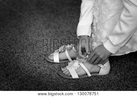 Young Girl doing buckle on white sandals dress