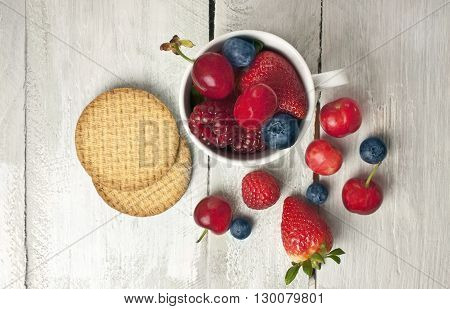 A white cup with fresh berries: cherries strawberries blueberries and raspberries with a couple of simple digestive cookies shot from above on a light wooden background texture