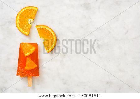 Homemade summer orange popsicle on white marble