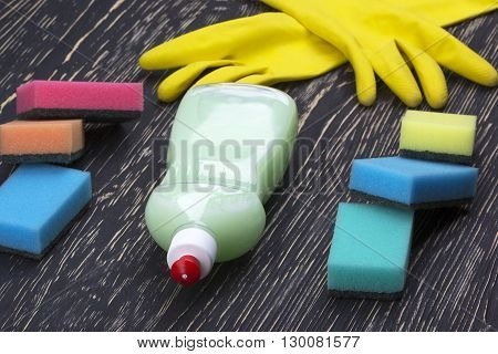 Detergent, sponges  and latex gloves on wooden background