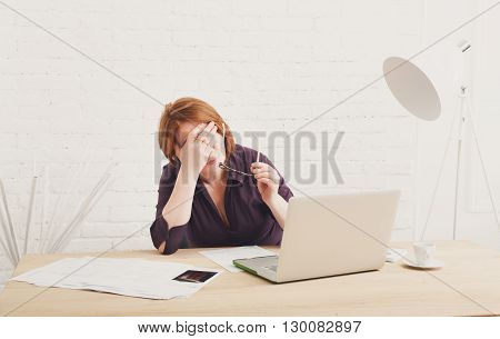Depressed and upset businesswoman in her office. Middle aged woman sad, frustrated