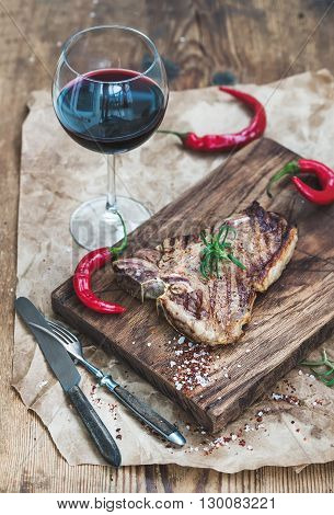 Cooked meat t-bone steak on serving board with roasted tomatoes, red chili peppers, fresh rosemary, spices and glass of red wine over rustic wooden background.
