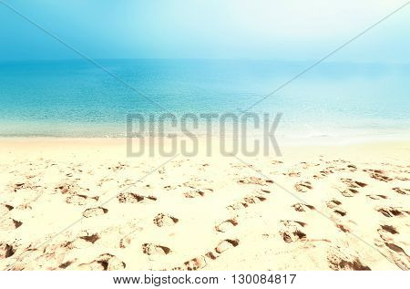 Beach background with foot prints on a sand / sea sand sky and summer day