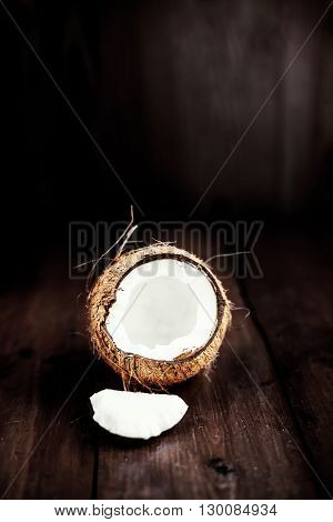 Coconut fruit cut in half with pieces / close up of a coconut on a wooden background with copy space