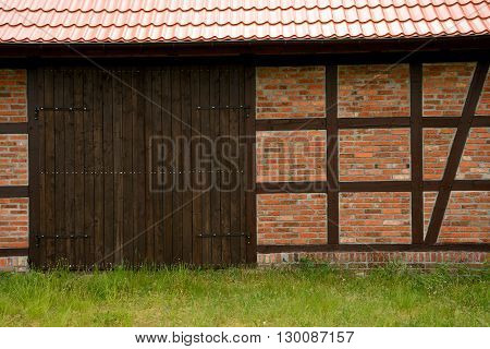 Prussian wall and brown wooden barn gate.